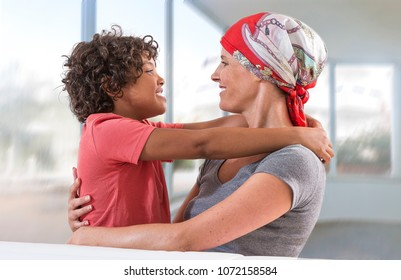 happy ill mother kissing her child boy againt a large windows living room