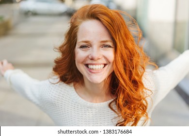 Happy impulsive young redhead woman grinning at camera as she leans forwards with her arms thrown back