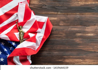 Happy Independence Day, American flag for Memorial Day 4th of July. The flag ruffled and Statue of Liberty on brown wooden.