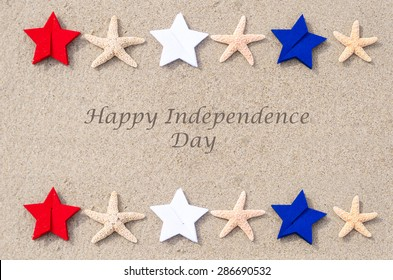 Happy Independence Day USA background with starfishes, red, blue and white stars on the sandy beach (4th of july holiday concept)