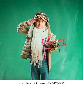 Happy Indian or asian boy kid playing with toy metal airplane in world war 2 pilot attire and glasses, saluting , standing isolated over green chalkboard