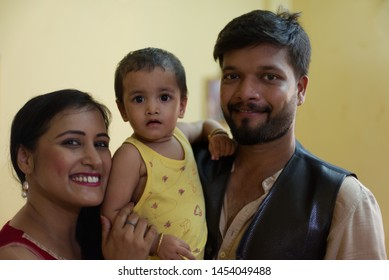 Happy Indian Bengali family with smiling mom, dad and baby. Indian lifestyle