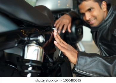 Happy Indian biker wearing leather jacket sitting on haunches and enjoying beauty of his new motorcycle, close-up shot