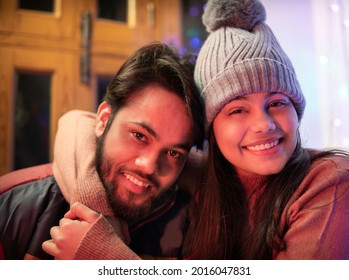 Happy Indian brother and sister sitting together at home in winters and embracing each other with a toothy smile and looking at the camera. They are wearing warm clothes, sweaters, jacket andcap.