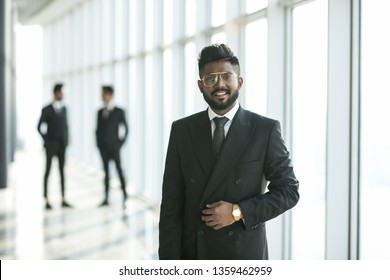 Happy indian business man in suit in office