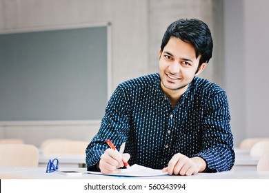 Happy indian business man writing with copy space