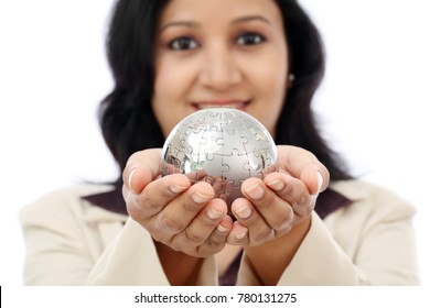 Happy Indian business woman holding puzzle globe