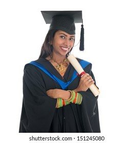 Happy Indian college student in graduation gown and cap holding diploma certificate. Portrait of mixed race Asian Indian and African American female model standing isolated on white background.