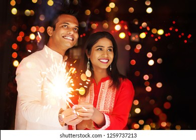 Happy Indian couple celebrating a festival and lighting bengal fire