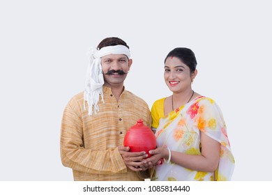 Happy Indian couple Holding a money Bank