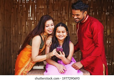 Happy Indian family with a 10 year old daughter using mobile phone together