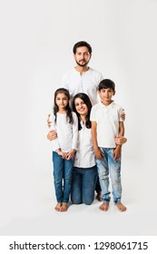 happy Indian family of 4 standing isolated over white background. Young couple with kids wearing white top and blue jeans. selective focus