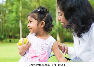 Happy Indian family. Asian girl holding an green apple at outdoor with mother.