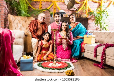 Happy Indian Family Celebrating Ganesh Festival or Chaturthi - Welcoming or performing Pooja and eating sweets in traditional wear at home decorated with Marigold Flowers - Shutterstock ID 1805592196