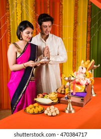 Happy Indian Family Celebrating Ganesh Festival or Chaturthi - Welcoming or performing Pooja and eating sweets in traditional wear at home decorated with Marigold Flowers