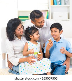 happy indian family enjoying eating ice cream indoor