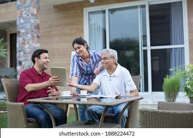Happy Indian family enjoying media content on digital tablet