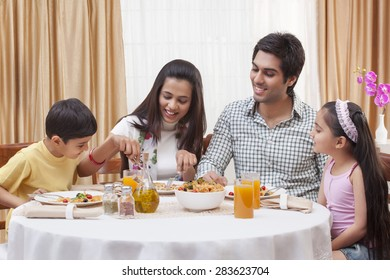 Happy Indian family having pizza together at restaurant