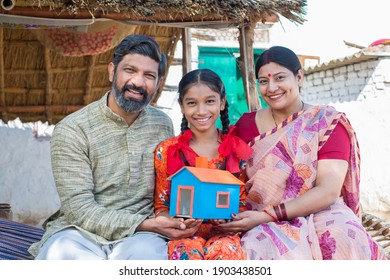 Happy Indian family holding a dream house model while sitting on traditional bed in village