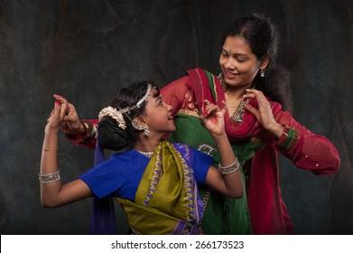 happy Indian family , mother instills daughter of folk culture