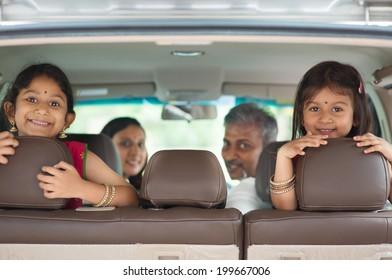 Bonne famille indienne assise en voiture, souriante, prête pour des vacances.  parents et enfants asiatiques.
