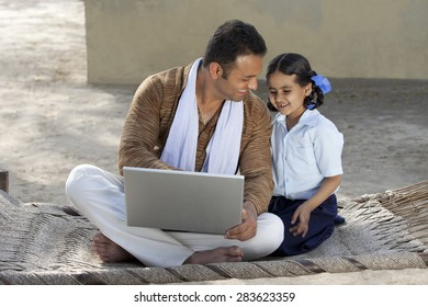 Happy Indian father and daughter using laptop