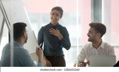 Happy indian female presenter feel grateful and pleased hearing employees sincere good words liking presentation, smiling woman speaker laugh with colleagues joking brainstorming at office briefing