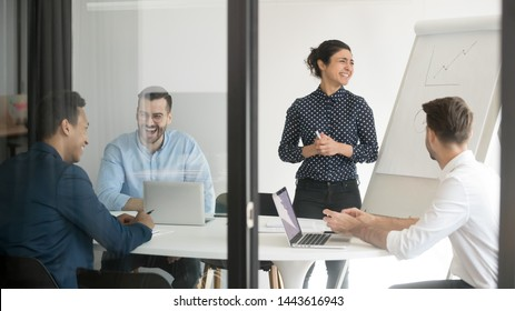 Happy indian female speaker presenter coach and male team employees laughing during flip chart presentation in conference room behind glass door, office fun and professional training education