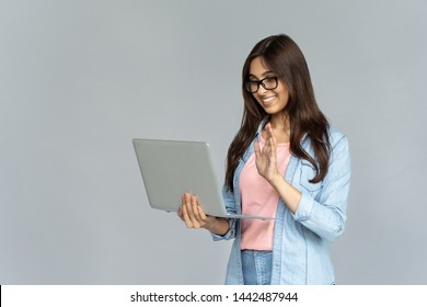 Happy indian girl holding using laptop looking at computer screen make conference online call, smiling young hindu woman user waving hand  doing internet video chat isolated on grey studio background