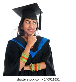 Happy Indian graduate student in graduation gown and cap thinking and smiling. Portrait of beautiful Asian female model standing isolated on white background.