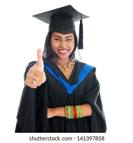 Happy Indian graduate student in graduation gown and cap giving thumb up hand sign. Portrait of beautiful Asian female model standing isolated on white background.