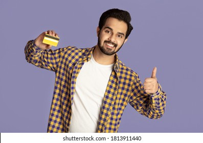 Happy Indian guy holding credit card and showing thumb up gesture on violet background