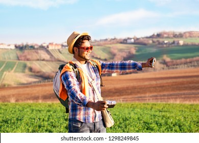 Happy indian hiker taking selfie using phone and old camera on fields background at sunset lights - Young asian tourist holding mobile standing in cultivated countryside - World travel concept - image