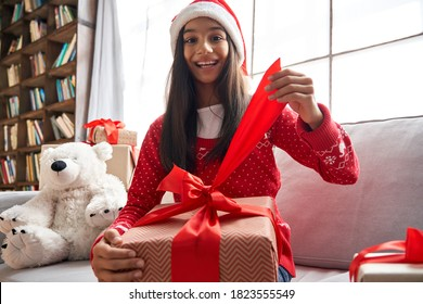 Happy indian kid girl opening gift video conference calling family, webcam chat view. Smiling latin child talking to camera virtual meeting social distance online friend celebrating Christmas at home.