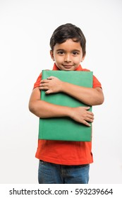 happy indian kid holding or hugging a big book over white background