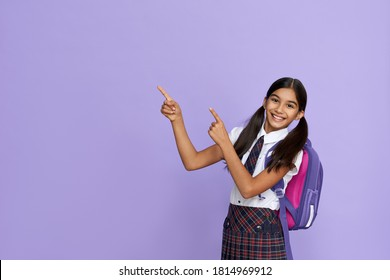 Happy indian kid primary elementary school girl with backpack wearing school uniform pointing fingers aside at copy space advertising products or services for pupils isolated on violet background.