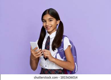 Happy indian kid school girl holding phone standing isolated on lilac background. Smiling latin preteen schoolgirl wearing school uniform, backpack, using mobile app on cellphone looking at camera.