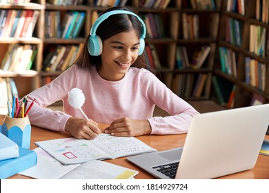 Happy indian latin preteen girl school pupil wearing headphones distance learning online at virtual class with teacher tutor on laptop by video conference call, watching tv lesson at home. - Shutterstock ID 1814929724