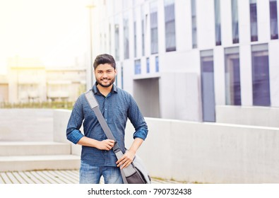 Happy indian male student standing with bag outdoor