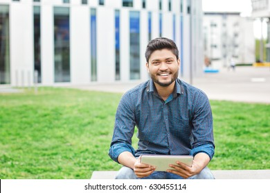 Happy indian male student with tablet