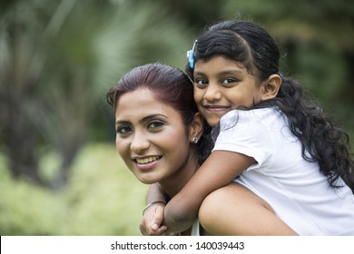 Happy Indian mother and daughter playing in the park. Lifestyle image.