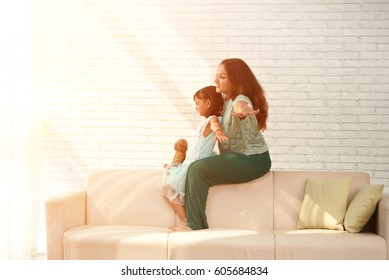 Happy Indian mother and daughter playing together in sunny living room