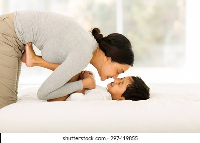 happy indian mother playing with her little boy on bed