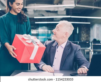 Happy Indian secretary congratulating boss with Christmas and presenting Christmas gift to him. Amazed senior businessman looking surprised. Gift-giving concept