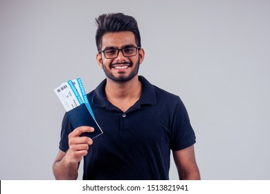 happy indian student male bearded wearing glasses and black t-short holding passport airline ticket yellow studio background . lifestyle summer trip concept.