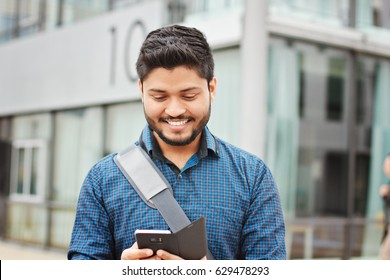 Happy indian student tetxting on smartphone at the campus