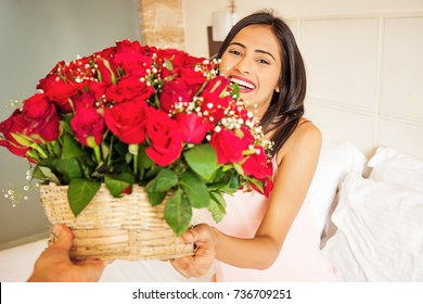 happy indian woman getting flowers delivery