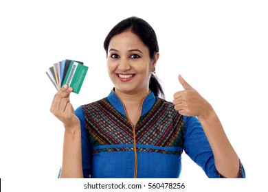 Happy Indian woman holding a bunch of debit cards-Cashless purchase concept