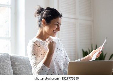 Happy Indian woman reading good news in letter, notification, holding paper, smiling girl rejoicing success, student excited by positive exam results, showing yes gesture, sitting on couch at home