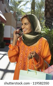 Happy Indian woman using cell phone while holding shopping bags